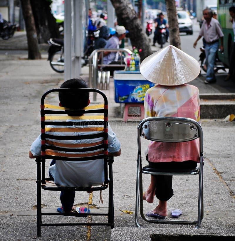 Verkäufer, die auf Straße am Stadtzentrum in Saigon, Vietnam sitzen lizenzfreies stockbild