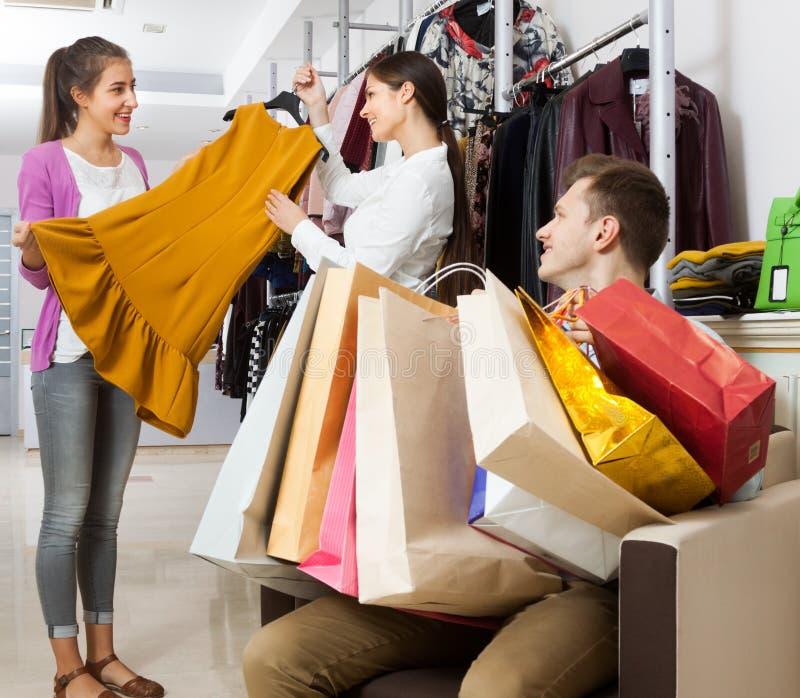 Verkäufer in einem Bekleidungsgeschäft bietet Kleid der jungen Frau an stockfotografie