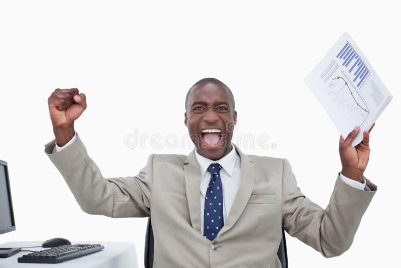Verkäufer mit den Fäusten oben beim Anhalten eines Diagramms stockbild