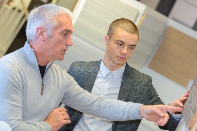 Verkäufer mit Kunden im Speicher für Baumaterialien stockfotografie
