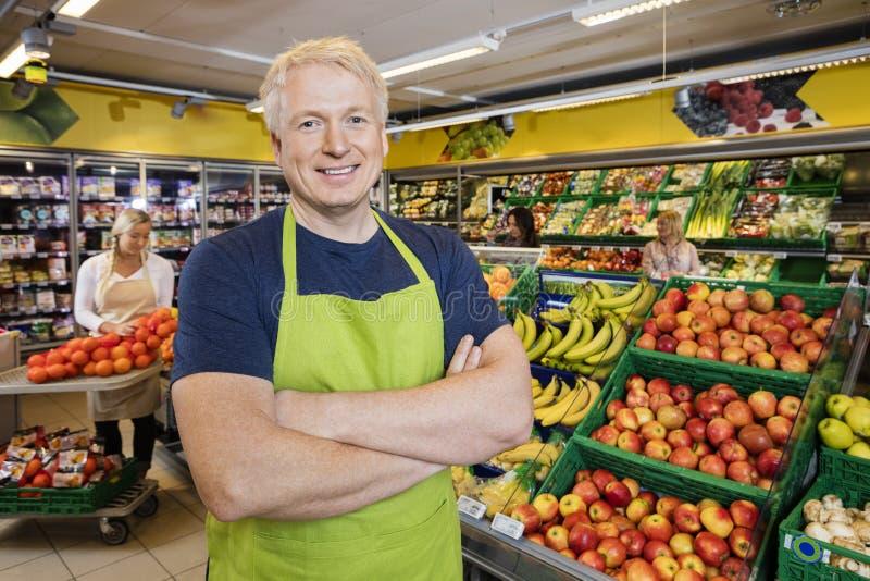 Verkäufer Standing Arms Crossed durch Früchte im Speicher lizenzfreie stockfotografie