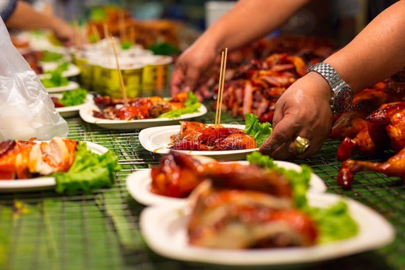 Verkäufer-Umhüllungs-Fleisch in den Platten am thailändischen Straßen-Lebensmittel stockbild