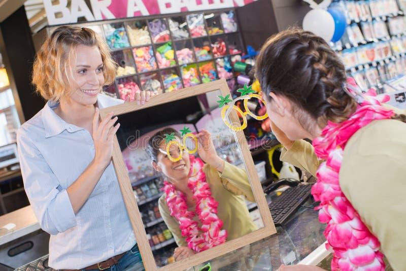 Verkäufer und Kunde, die lustige Rahmen auf Spielzeugsladen betrachten lizenzfreie stockfotografie