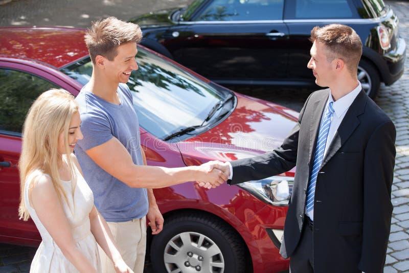 Verkäufer und Paare, die mit dem Auto Hände rütteln stockbilder