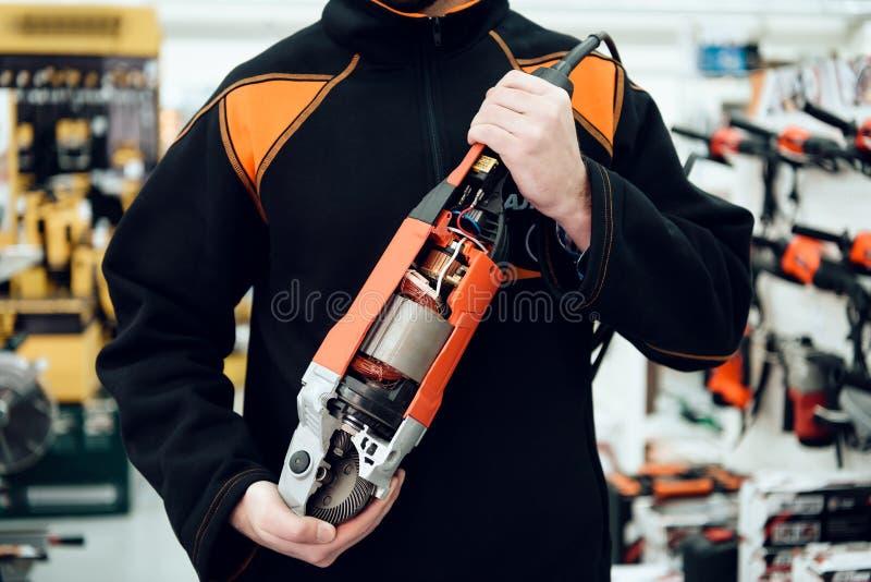 Verkäufer wirft mit neuem Tellerschleifer im Elektrowerkzeugspeicher auf stockbilder