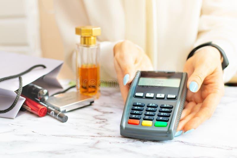 Verkäuferfrau in einem weißen Hemd hält einen kontaktlosen Zahlungsanschluß in ihren Händen in Kosmetik und Parfümeriespeicher lizenzfreie stockbilder