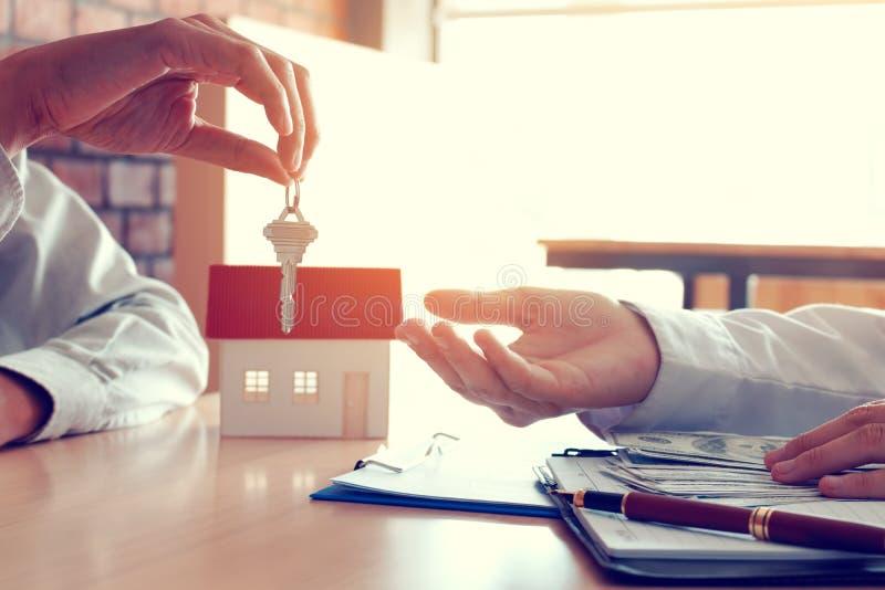 Verkäuferhauptmakler stellen Schlüssel zu neuen Hausbesitzern und zu Käufern g zur Verfügung stockbild