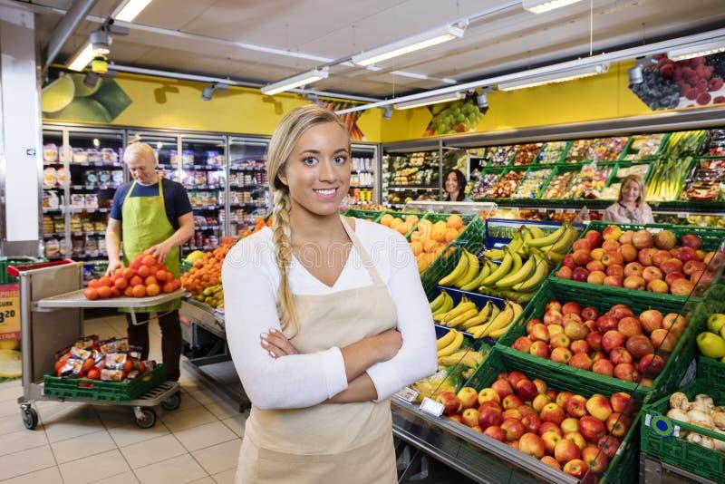 Verkäuferin With Arms Crossed durch Frucht-Kisten im Gemischtwarenladen stockfoto