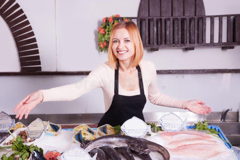Verkäuferin bietet frische Fische an lizenzfreies stockfoto