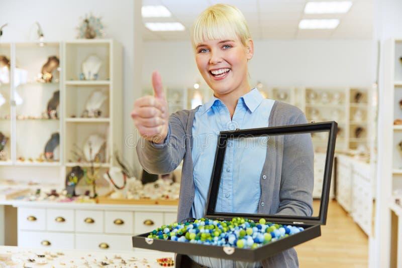 Verkäuferin in der Juweliergeschäftholding stockfotografie