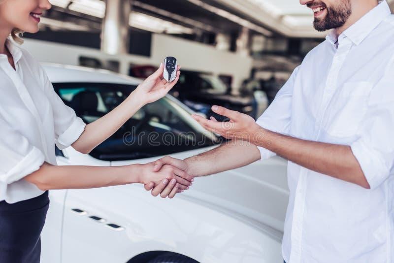 Verkäuferin, die dem männlichen Kunden Schlüssel des Autos gibt lizenzfreie stockfotografie