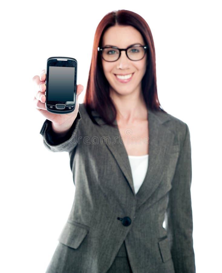 Verkäuferin, die spätesten mobilen Hörer anzeigt lizenzfreies stockbild