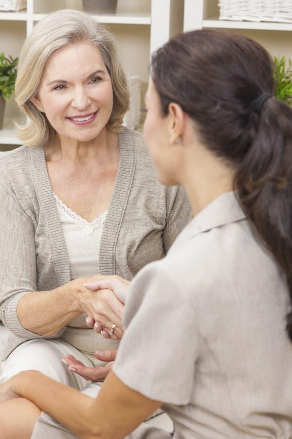Verkäuferin, die zu Hause Hände mit älterer Frau rüttelt stockbilder