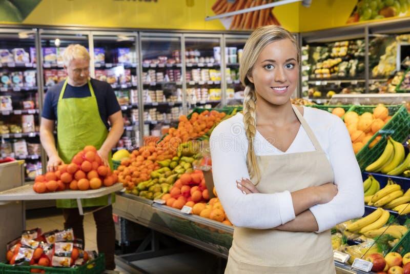 Verkäuferin Standing Arms Crossed während Kollege, der Orange stapelt stockfotos