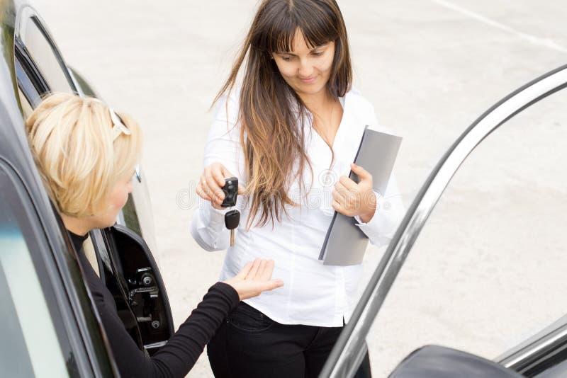 Verkäuferin, welche die Schlüssel zu einem Neuwagen überreicht lizenzfreies stockfoto