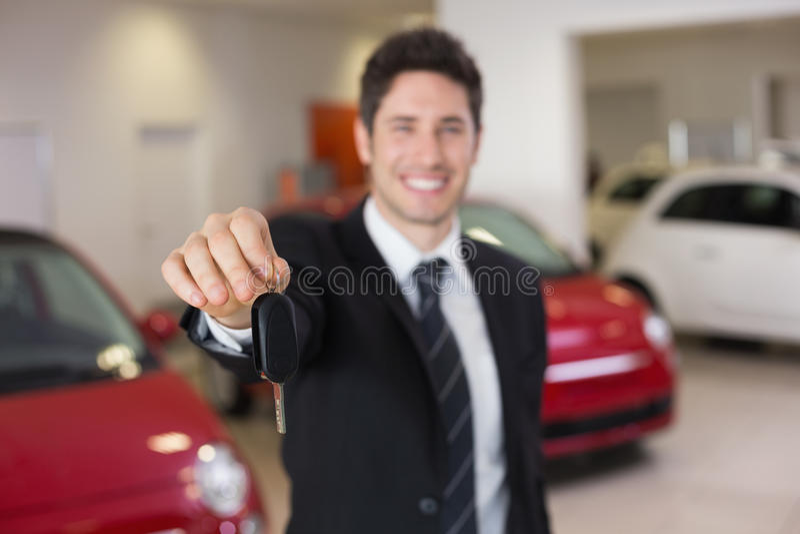 Verkäuferstellung beim Angebot von Autoschlüsseln stockfotografie