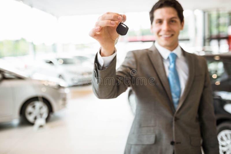 Verkäuferstellung beim Angebot von Autoschlüsseln lizenzfreie stockbilder