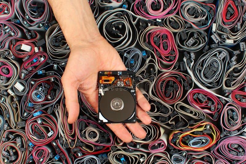 Verkabelt offenes Festplattenlaufwerk der Handholding, gegen Computer lizenzfreie stockfotografie