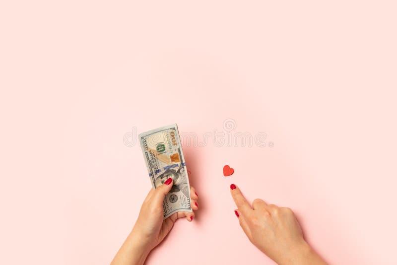 Verkauf des Liebessymbols Die menschliche Hand hält Geld in einer Hand und in einem roten Herzen in der anderen stockfoto