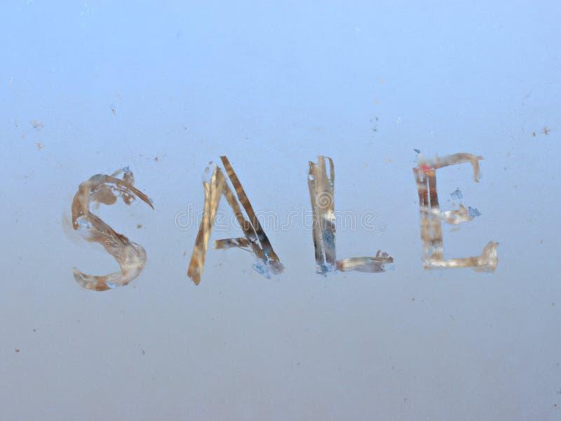 Verkauf geschrieben auf eisiges Winterfenster stockfoto