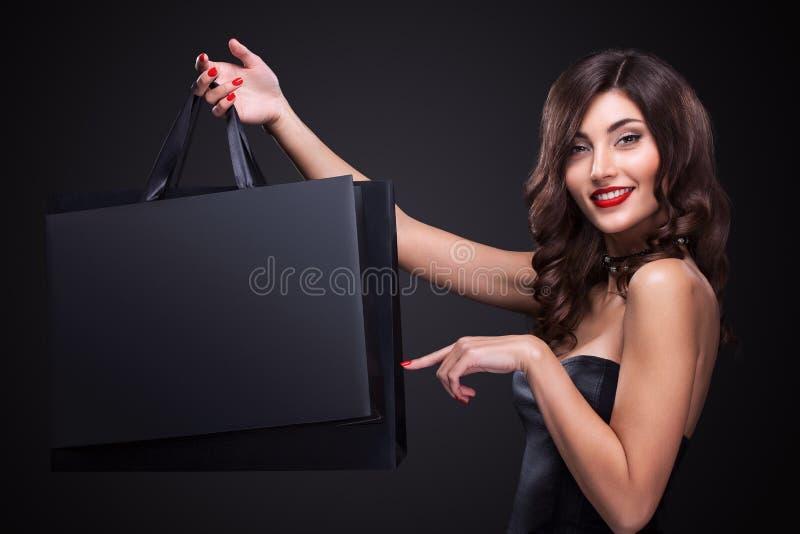 Verkauf Junge lächelnde Frau, die Einkaufstasche in schwarzem Freitag-Feiertag zeigt Mädchen auf dunklem Hintergrund mit Kopienra lizenzfreie stockfotografie