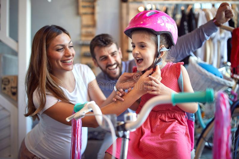 Verkauf, Verbraucherschutzbewegung und Leutekonzept - Frau, die neues Fahrrad und Sturzhelm f?r wenig M?dchen im Fahrradgesch?ft  stockbilder