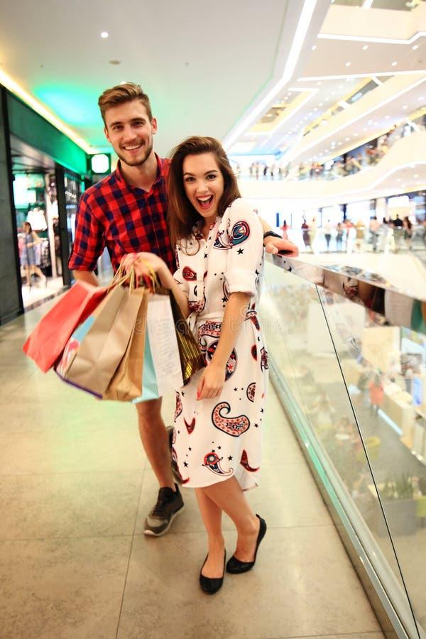 Verkauf, Verbraucherschutzbewegung und Leutekonzept - glückliches junges Paar mit den Einkaufstaschen, die in Mall gehen lizenzfreie stockfotos