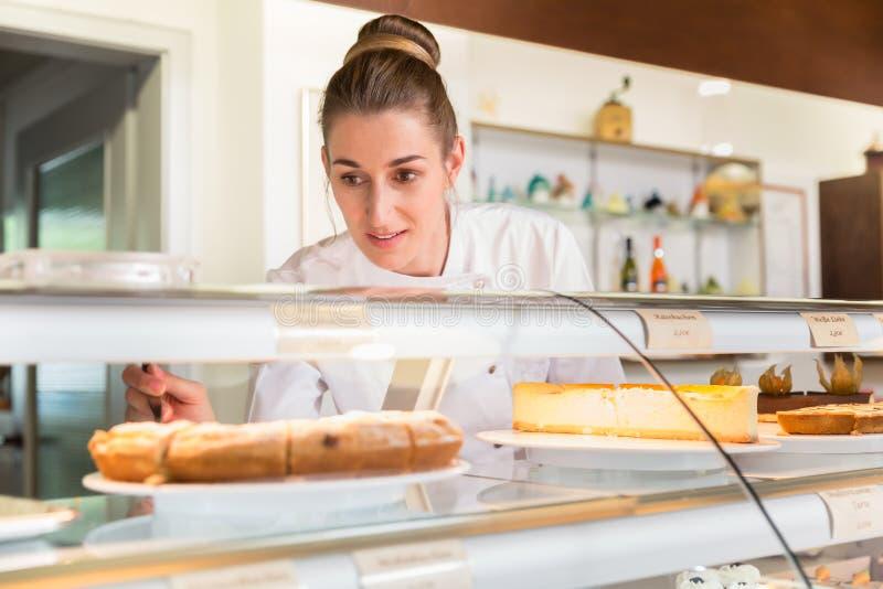 Verkaufsfrau im Bäckereishop, der Kuchen auf Anzeige setzt stockfotografie