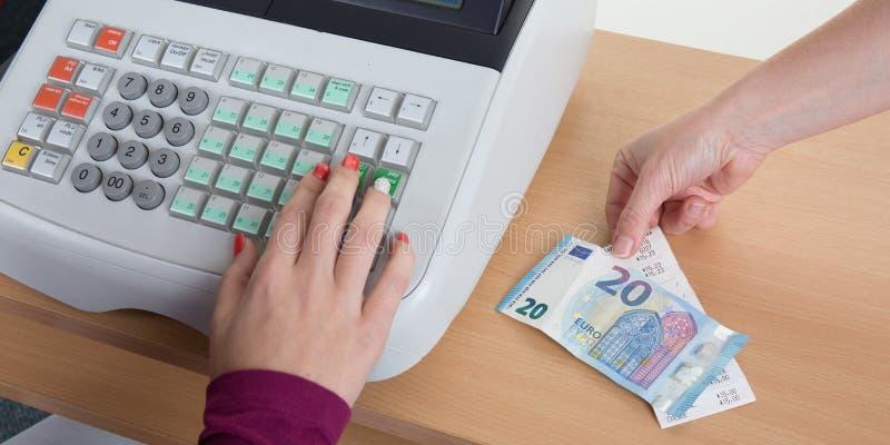 Verkaufsfrauenhände an der Registrierkasse mit Euro prägt Banknoten lizenzfreie stockbilder