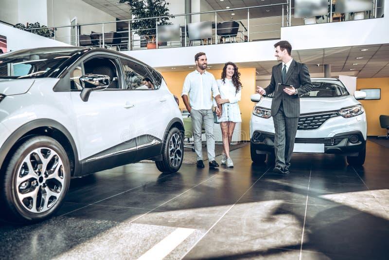 Verkaufsleiter, welche jungen Paaren hilft, um einen Neuwagen zu wählen stockbild