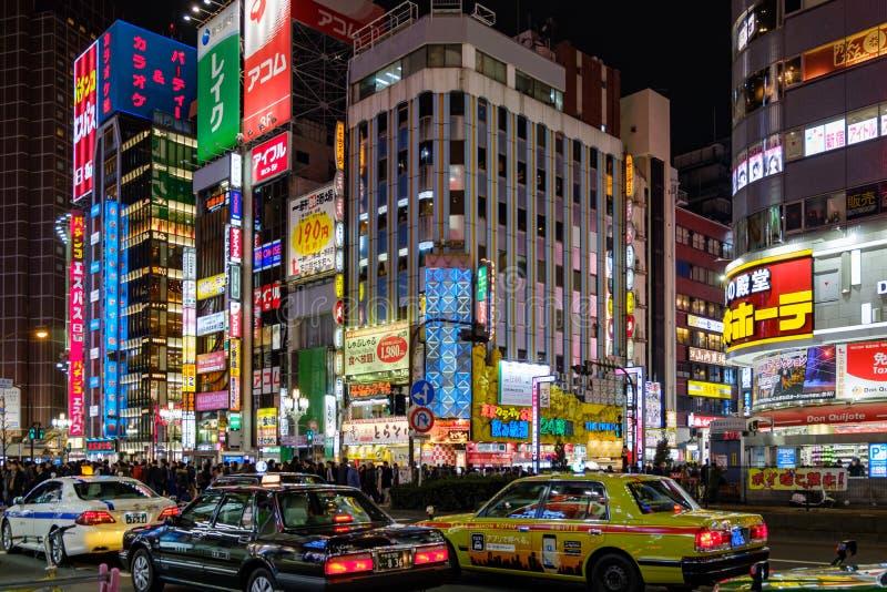 Verkeer en taxi bij verkeerslicht in Shinjuku-district bij nacht wordt tegengehouden die royalty-vrije stock foto