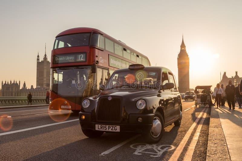 Verkeer en willekeurige mensen op de Brug van Westminster in zonsondergang, Londen, het UK stock foto's