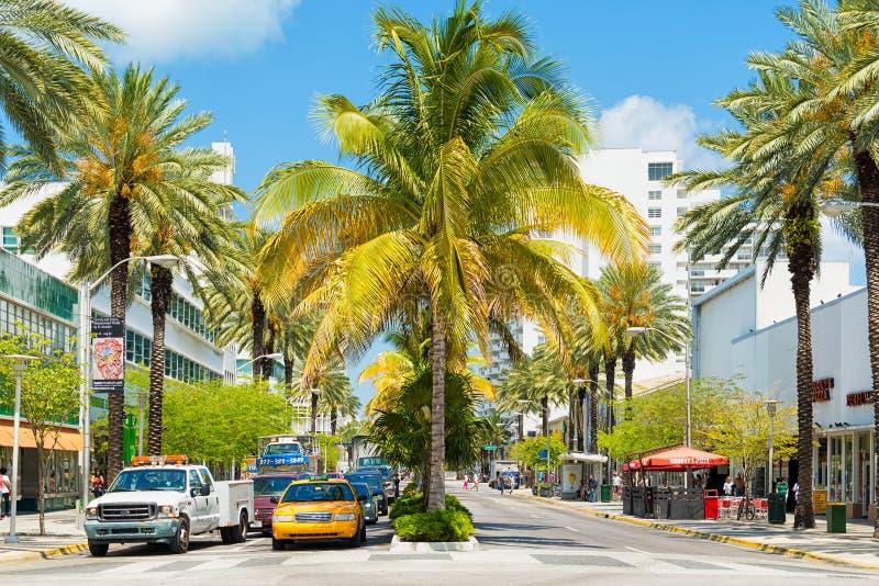 Verkeer en winkels onder tropische palmen in Lincoln Road binnen royalty-vrije stock fotografie