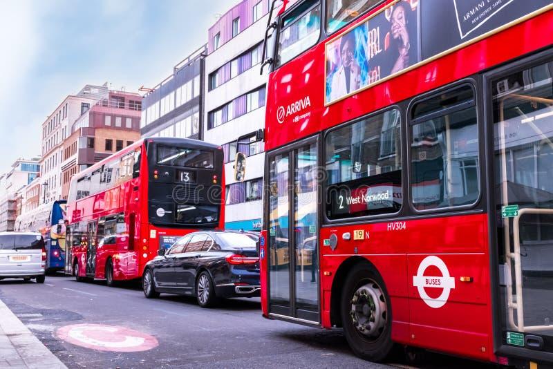 Verkeer in Londen - twee typische rode bussen met advertenties, zwart Mercedes, grijze auto royalty-vrije stock fotografie