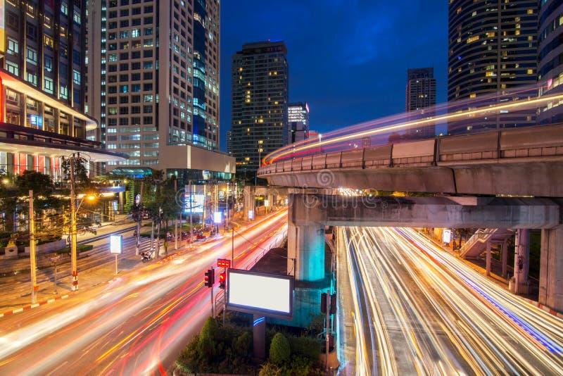 Verkeerslicht en hemeltrein in bezige lichte slepen bij nacht stock afbeeldingen