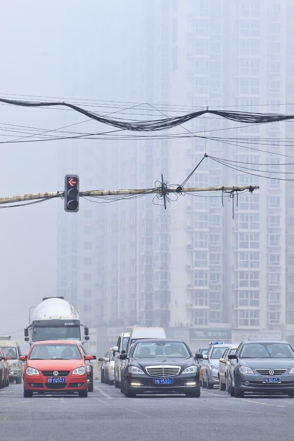 Verkeerslicht met het wachten auto's, dikke laag van smog, Peking, China stock afbeelding