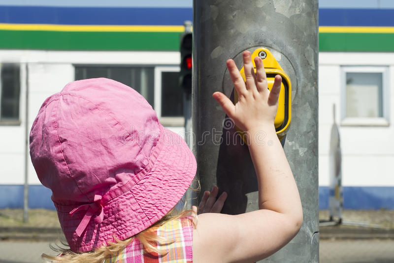 Verkeersregels op de straat voor voetgangers Kinderen Het meisje bij het verkeerslicht drukt de knoop Hete zonnige dag stock afbeeldingen
