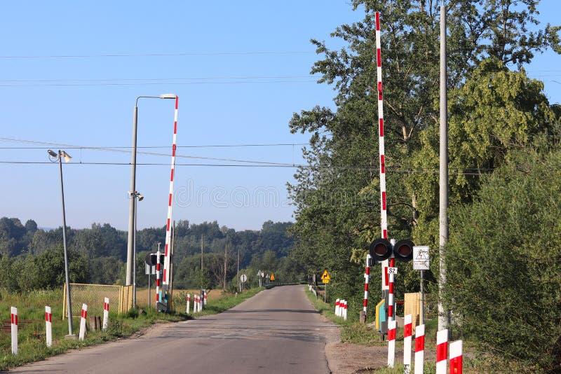 Verkeersteken bij de spoorwegovergang met een barrière Organisatie van het vervoersysteem van een Europees land Rode witte kleuri royalty-vrije stock fotografie