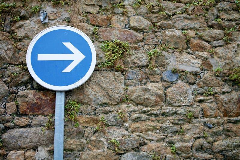 Verkeersteken juiste pijl op de oude achtergrond van de steenmuur stock fotografie