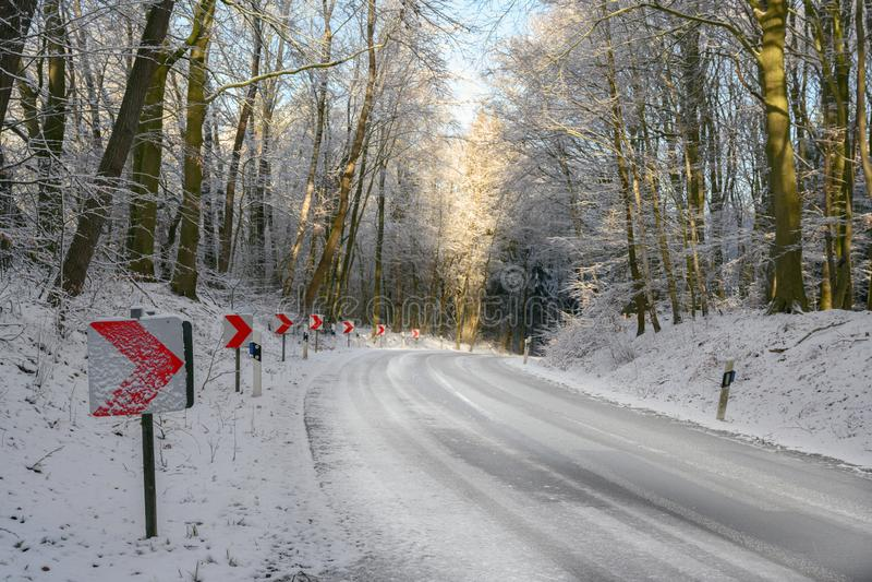 Verkeersteken met rode pijlen op een gevaarlijke kromme op een sneeuwlandweg door het de winterbos, veiligheids drijfconcept, royalty-vrije stock foto's
