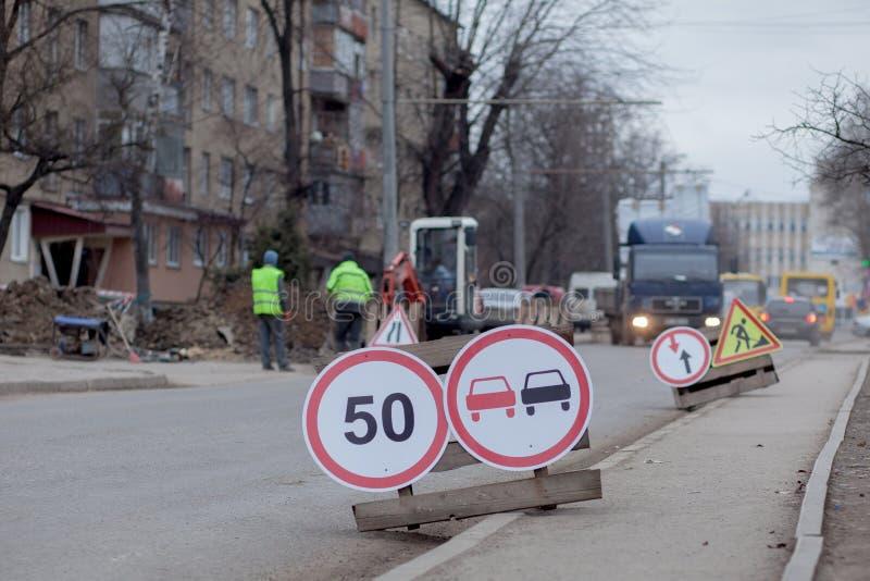 Verkeersteken, omweg, wegreparatie op straatachtergrond, vrachtwagen en graafwerktuig gravend gat stock foto