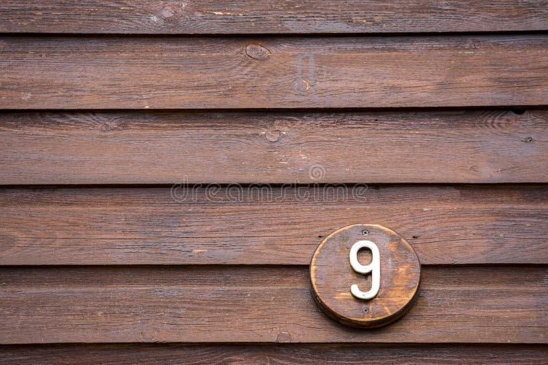 Verkeersteken op een huis die aantal negen lezen die uit hout wordt gemaakt stock foto