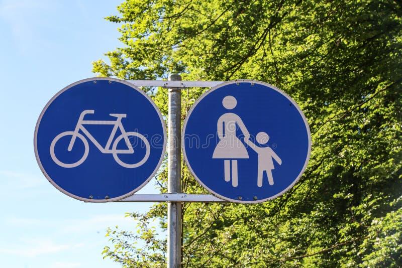 Verkeersteken richten aan een voetpad en een fietsweg stock afbeelding