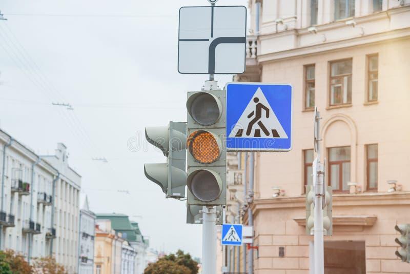 Verkeersteken van een voetgangersoversteekplaats en een verkeerslicht met geel licht royalty-vrije stock foto