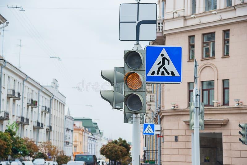 Verkeersteken van een voetgangersoversteekplaats en een verkeerslicht met geel licht royalty-vrije stock fotografie
