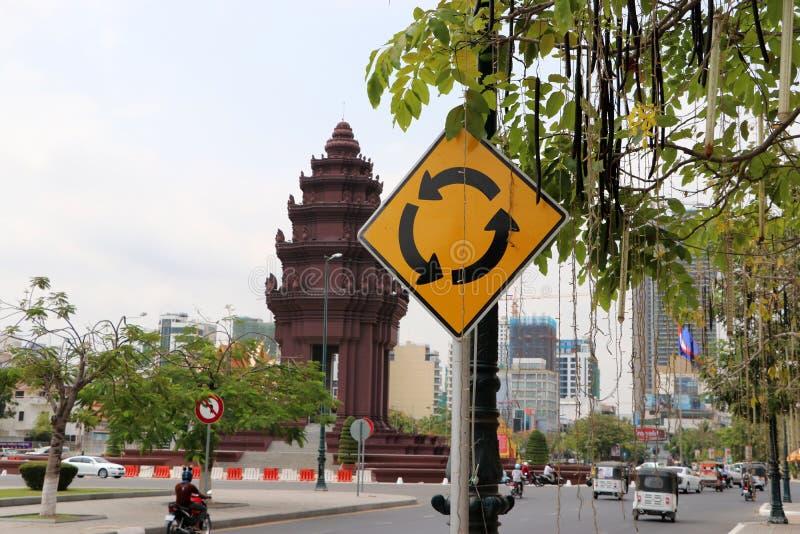 Verkeersteken van rotonde en het Onafhankelijkheidsmonument, herdenkings Cambodjaanse Onafhankelijkheidsdag na het winnen van de  royalty-vrije stock afbeelding