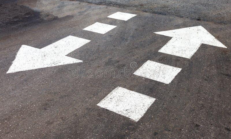 Verkeersteken witte pijlen op asfaltweg stock afbeeldingen