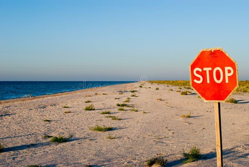 Verkeerstekeneinde die zich op van de overzeese van het strandzand de blauwe zon hemel lege zomer bevinden royalty-vrije stock foto's