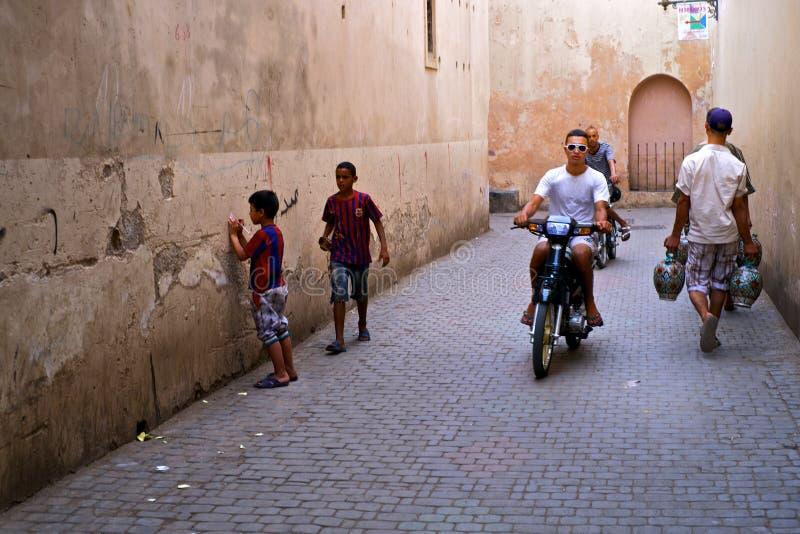 Verkehrsreiche Straße an der historischen Stadt mit lokalen Leuten mit Vasen und Jungen auf einem Motorrad stockbilder