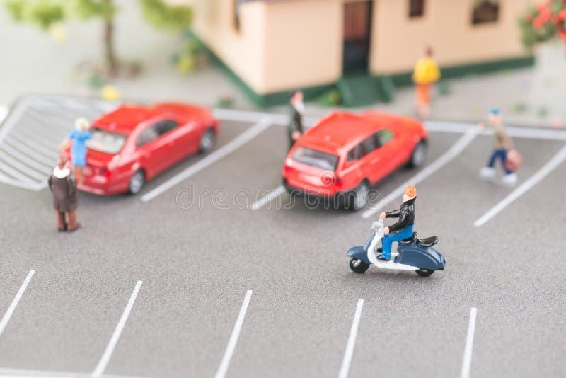 Verkehrsreiche Straße mit Miniaturleuten, Autos und Roller stockfotos